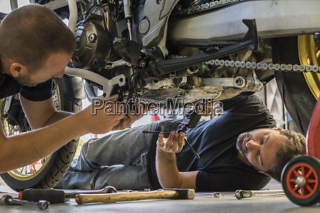 mechaniker arbeitet auf motorrad in der