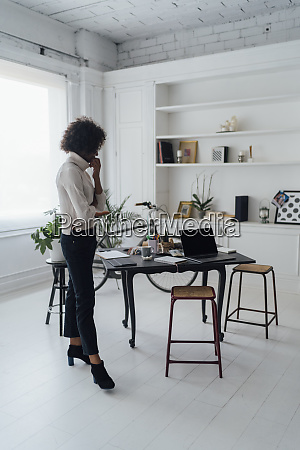 freelancer standing in her home office