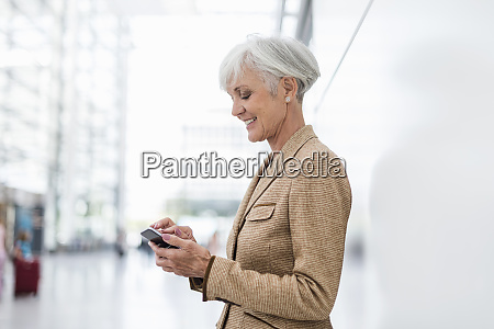 smiling senior businesswoman using cell phone