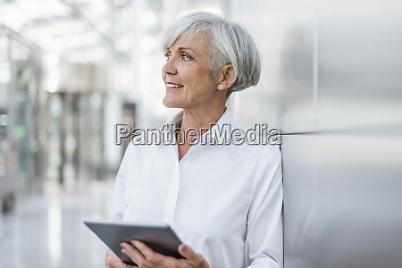 portrait of smiling senior businesswoman holding