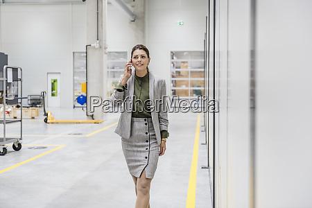 businesswoman walking in factory workshop talking