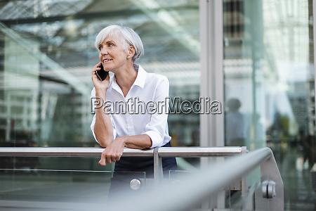 senior businesswoman leaning on railing in