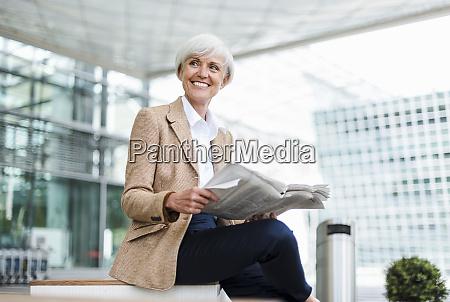 laechelnde seniorin sitzt in der stadt