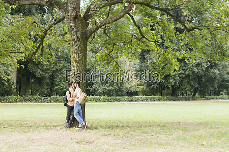 kissing young gay couple leaning against