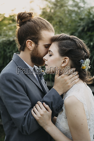affectionate bride and groom outdoors