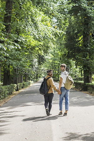 young gay couple with backpacks walking