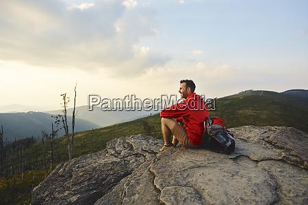 man sitting on rock enjoying the