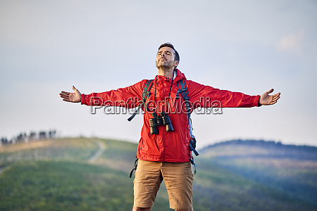 man standing with outstretched arms on