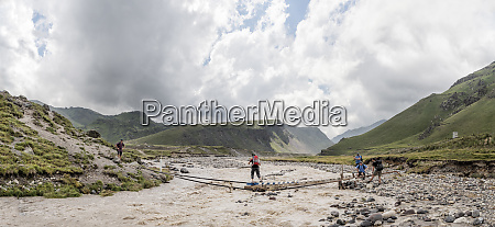 russia caucasus mountaineers crossing river in