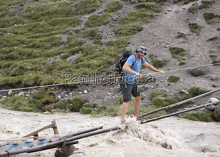 russia caucasus mountaineer crossing river in