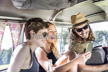 happy friends inside van looking at