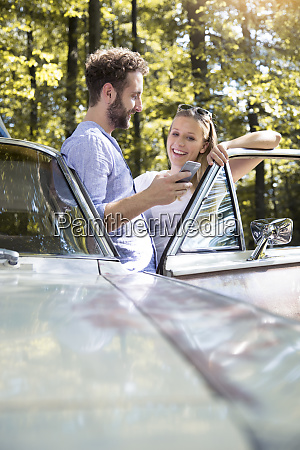 smiling young couple with cell phone