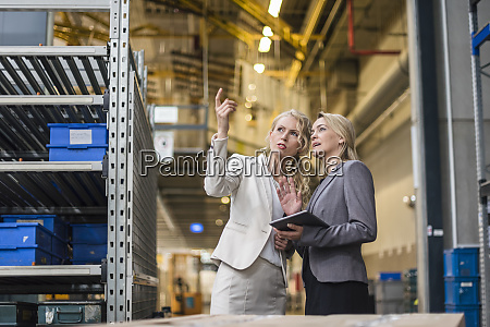 two women with tablet talking in