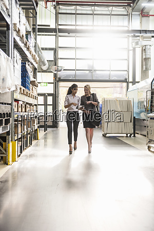 two women with tablet walking and