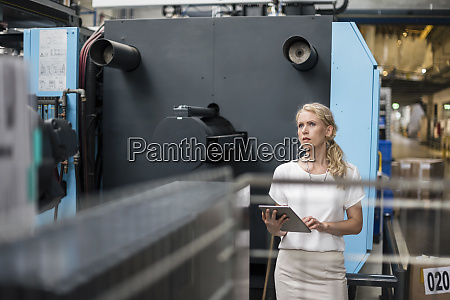 woman with tablet at machine in