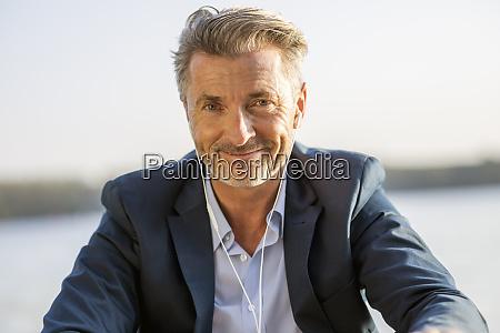portrait of smiling businessman with earphones