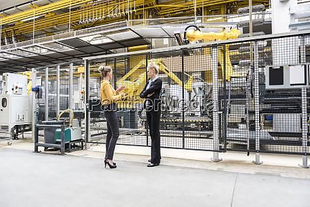 two women talking in factory shop