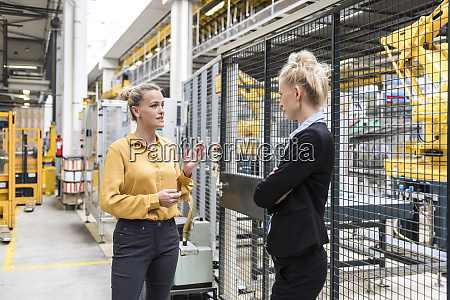 two women talking in factory shop