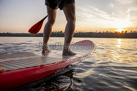 legs of man standing on paddleboard