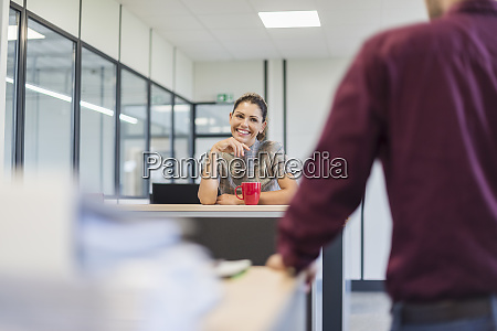 female employee sitting at desk talking