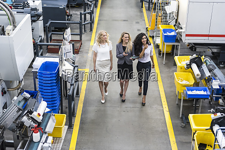 three smiling women with tablet walking