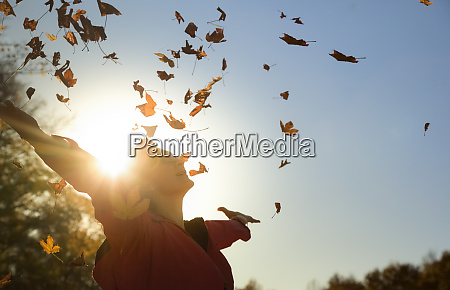 woman throwing up autumn leaves at