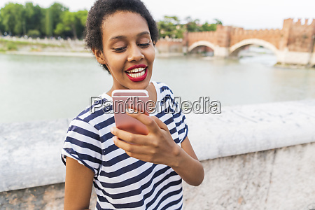 smiling young woman using cell phone