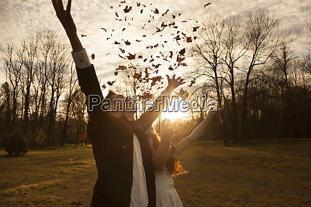 happy bridal couple in park cheering