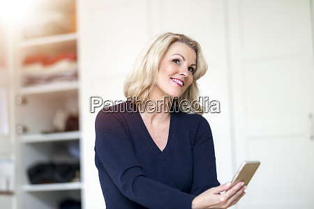 portrait of smiling blond woman using