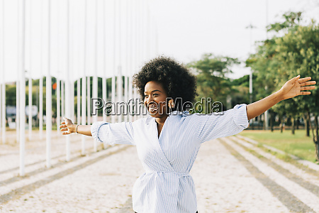 carefree young woman with arms outstretched