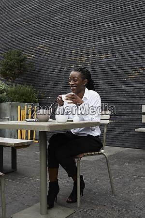 lachende geschaeftsfrau sitzt auf der terrasse