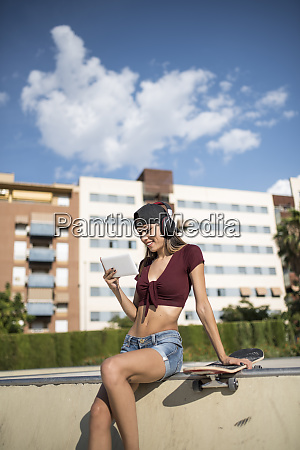 young pretty woman sitting on wall