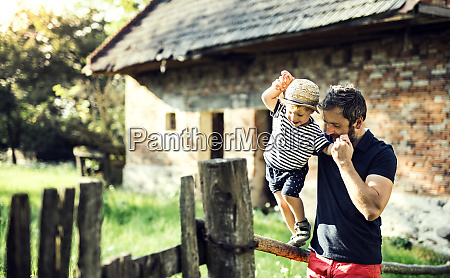 father assisting his little son in