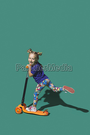playful girl riding scoter on green