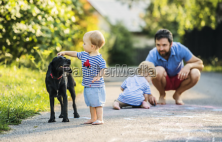 baby girl stroking dog while father