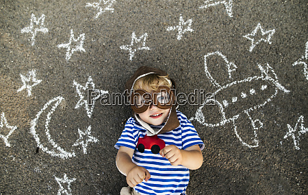 portrait of smiling toddler wearing pilot