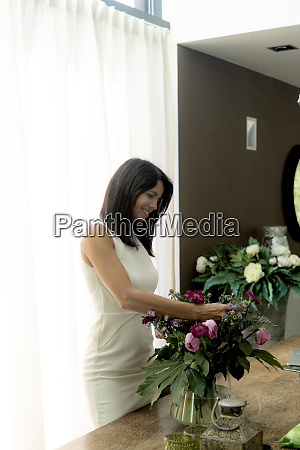 smiling dark haired woman arranging flowers