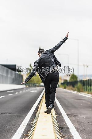 rear view of punk woman balancing