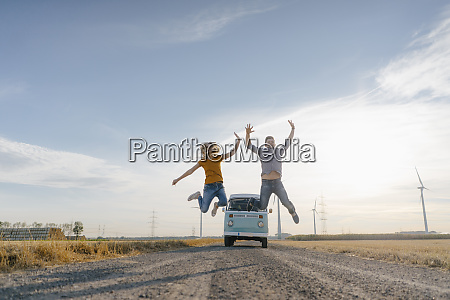 exuberant couple jumping on dirt track