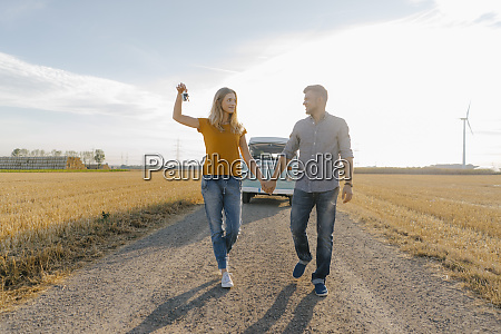 young couple with car key walking