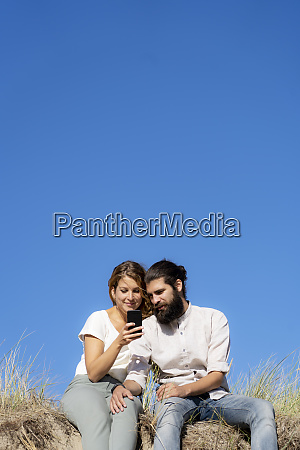 young couple sitting on a dune