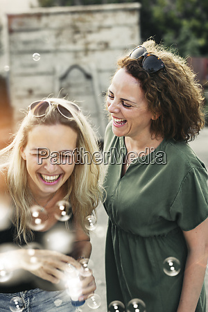 two happy women with soap bubbles