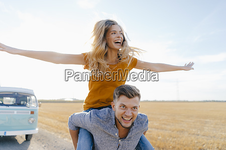 playful young couple at camper van