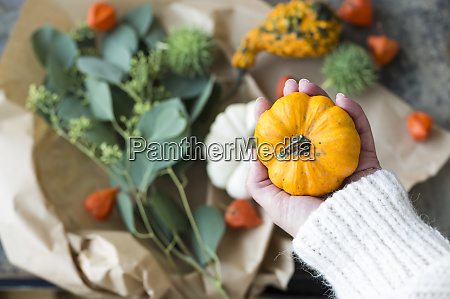 autumnal decoration womans hand holding ornamental
