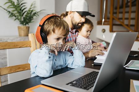 vater arbeitet zu hause mit laptop