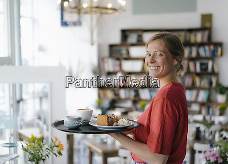 portrait of smiling young woman serving
