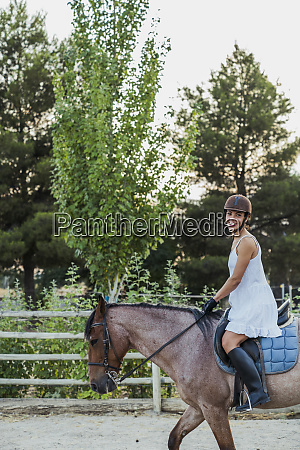 glueckliche frau reitet auf dem pferd