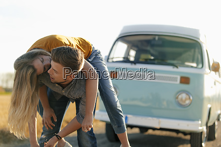 playful young couple at camper van