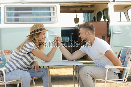 happy young couple armwrestling on camping