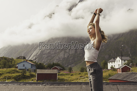 young woman standing in nature stretching